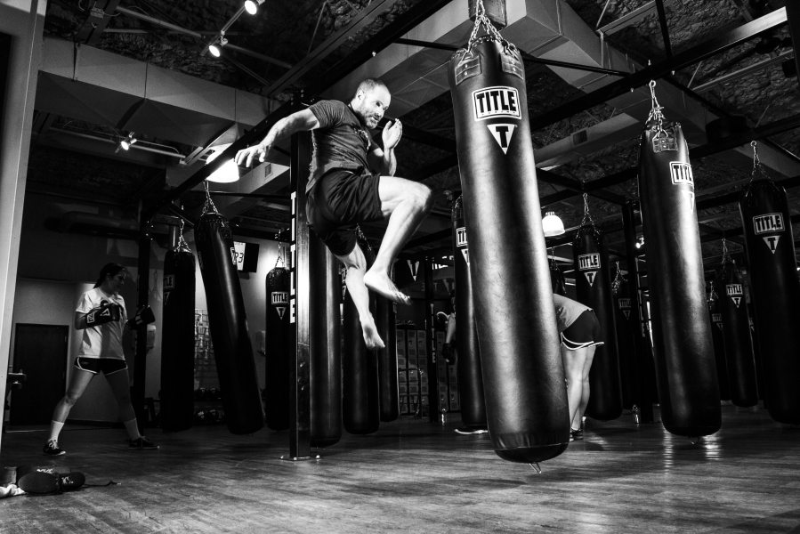 A confident man kicking a punching bag