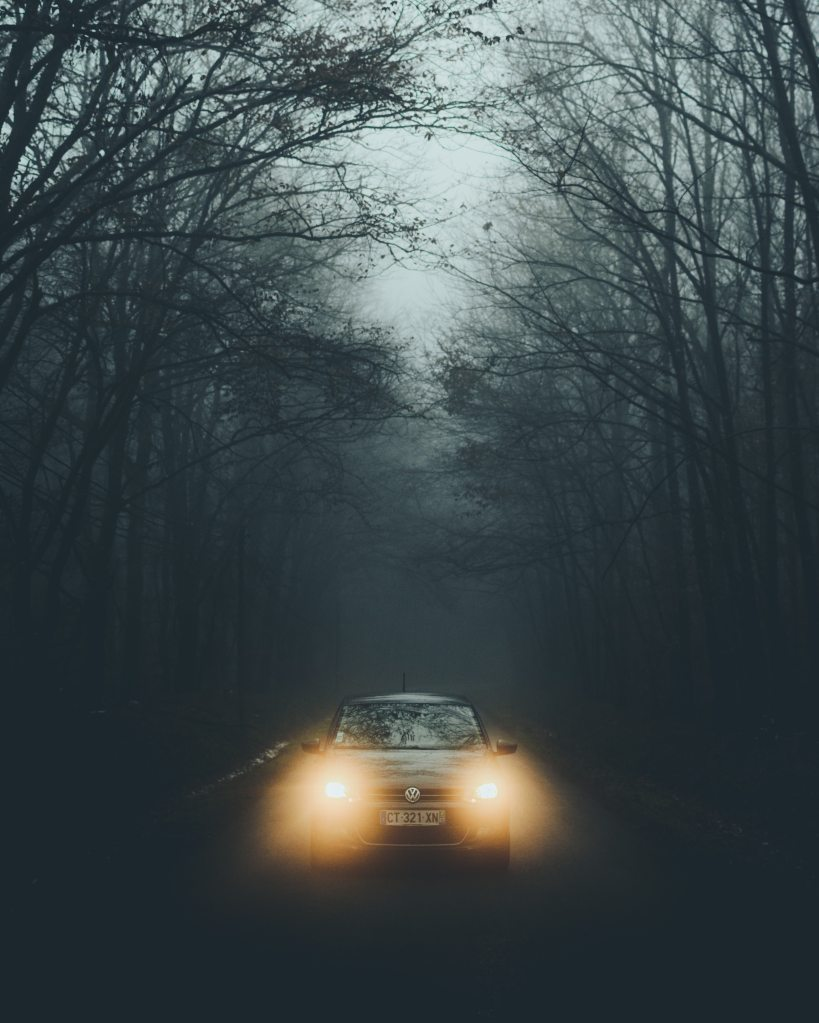 A car with its lights on in the fog