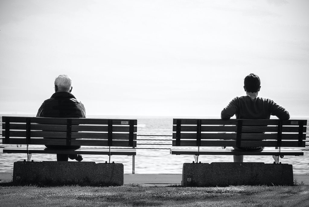 two people waiting on benches